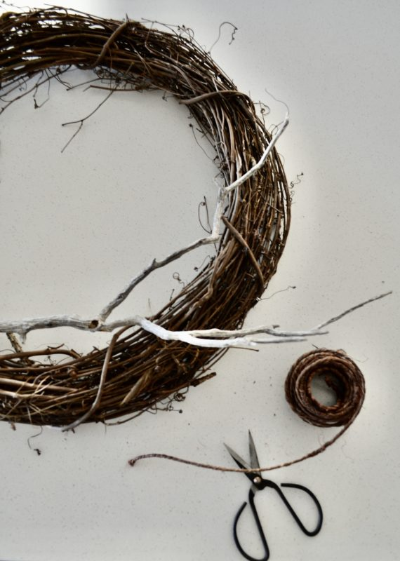 Add twig to wreath for halloween
